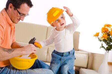babyboy: Father and child playing construction game together at home.