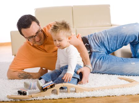 Father and kid playing together on floor of livingroom, smiling. photo