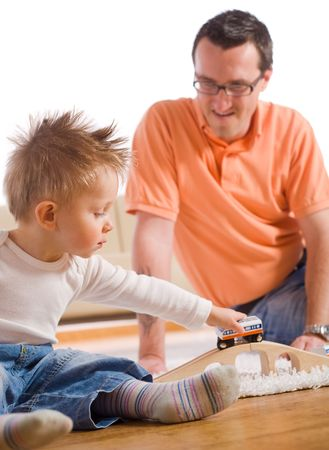 Father and little kid playing together with toy train in living room. photo