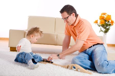 Father and baby boy playing together at home, sitting on floor. photo
