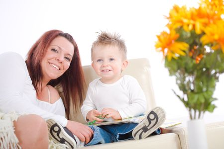 Happy family sitting on sofa at home mother reading for baby boy from story book. photo