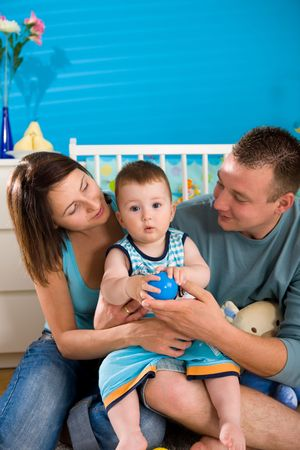 Portrait of happy family at home. Baby boy ( 1 year old ) and young parents father and mother sitting on floor and playing together at childrens room, smiling. photo