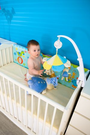 Cute baby boy ( 1 year old ) playing in baby bed at children's room, looking up. Stock Photo - 5943355