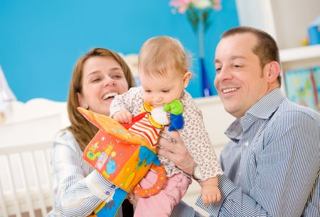 Happy family playing together: mother, father and 1 year old baby girl at children's room, smiling. Toys are officially property released. Stock Photo - 5943543
