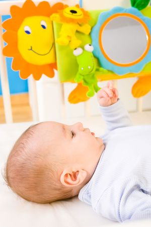 Infant baby lying in baby bed at childrens room. Toys are officially property released. photo