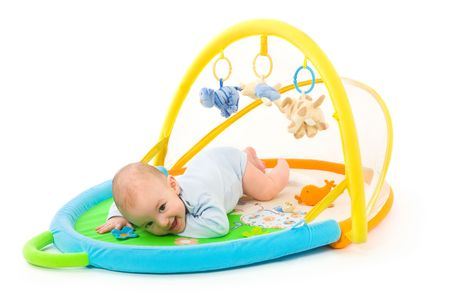 soft toy: Happy baby playing in baby gym toy, isolated on white background.
