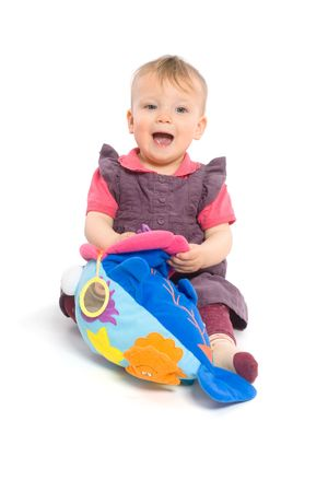Cute baby girl (1 year old) sitting on floor playing with stuffed animal toy.  Isolated on white, smiling. Toys are offically property released. Stock Photo - 5943540