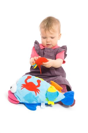 Cute baby girl (1 year old) sitting on floor playing with stuffed animal toy.  Isolated on white, smiling. Toys are offically property released. photo