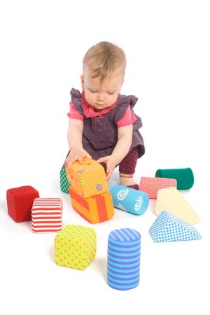 9 months old: TOYS ARE PROPERTY RELEASED. Little baby girl (9 months old) playing with toy blocks. Isolated on white.