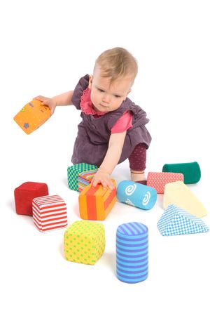 9 months: TOYS ARE PROPERTY RELEASED. Little baby girl (9 months old) playing with toy blocks. Isolated on white.