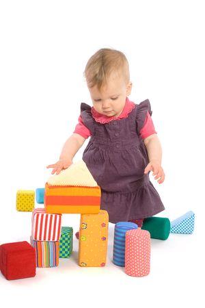 9 months old: LOS JUGUETES SON PROPIEDAD LANZADO. Ni�a de beb� (9 meses) jugando con bloques de juguete. Aislados en blanco.  Foto de archivo