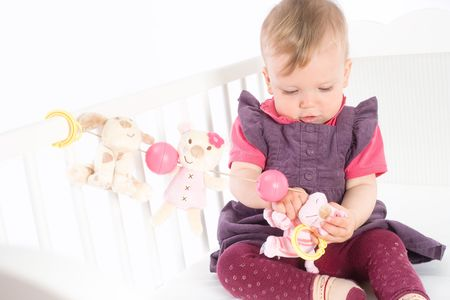 Cute baby girl (1 year old) sitting on crib, holding soft toys. Isolated on white, smiling. Toys are offically property released. Stock Photo - 5943579