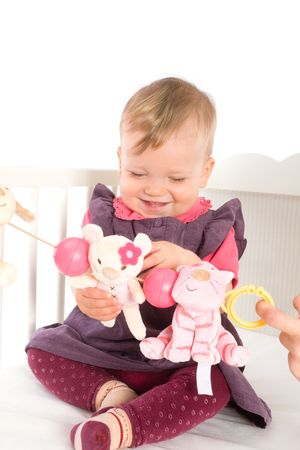 Cute baby girl (1 year old) sitting on crib, holding soft toys. Isolated on white, smiling. Toys are offically property released. photo