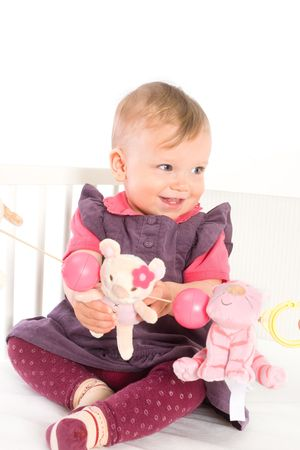 Cute baby girl (1 year old) sitting on crib, holding soft toys. Isolated on white, smiling. Toys are offically property released. Stock Photo - 5943593