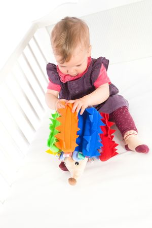 Happy cute baby girl (9 months) sitting on bed and playing with soft toy, smiling. Toys are property released. Stock Photo - 5943567
