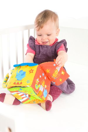 Happy cute baby girl (9 months) sitting on bed and playing with soft toy, smiling. Toys are property released. Stock Photo - 5943589