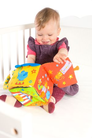 Happy cute baby girl (9 months) sitting on bed and playing with soft toy, smiling. Toys are property released. Stock Photo - 5943573