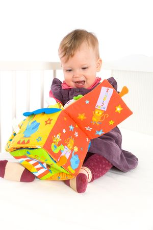 Happy cute baby girl (9 months) sitting on bed and playing with soft toy, smiling. Toys are property released. photo