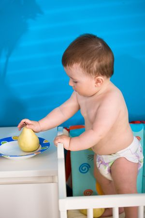Sweet baby boy ( 1 year old ) in diaper standing on baby bed and eating healthy fruits. Stock Photo - 5943535