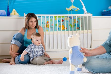 Portrait of happy family at home. Baby boy ( 1 year old ) and young parents father and mother sitting on floor and playing together at children's room, smiling. Stock Photo - 5943508