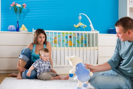 Portrait of happy family at home. Baby boy ( 1 year old ) and young parents father and mother sitting on floor and playing together at children's room, smiling. Stock Photo - 5943596