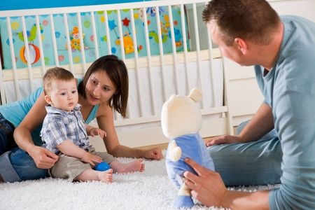 Portrait of happy family at home. Baby boy ( 1 year old ) and young parents father and mother sitting on floor and playing together at children's room, smiling. Stock Photo - 5943602