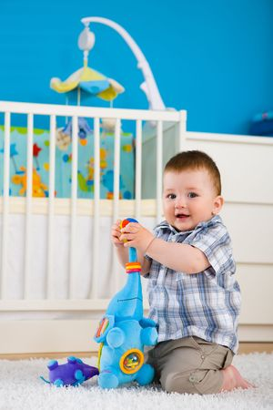 Happy baby boy ( 1 year old ) sitting on floor at home and playing with soft toys at children's room, smiling. Stock Photo - 5943570