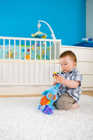 Sweet baby boy ( 1 year old ) sitting on floor at home and playing with soft toys at childrens room. photo