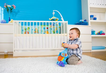 family rooms: Sweet baby boy ( 1 year old ) sitting on floor at home and playing with soft toys at childrens room.
