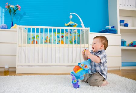 Happy baby boy ( 1 year old ) sitting on floor at home and playing with soft toys at children's room, smiling. Stock Photo - 5943572