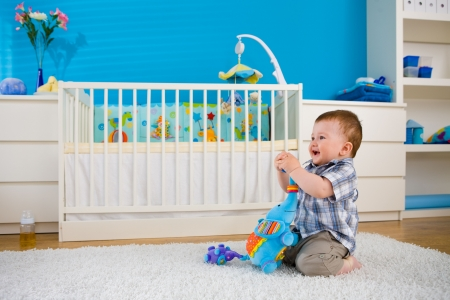 Happy baby boy ( 1 year old ) sitting on floor at home and playing with soft toys at children's room, smiling. Stock Photo - 5943580