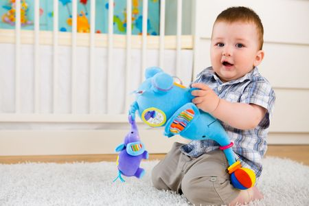Happy baby boy ( 1 year old ) sitting on floor at home and playing with soft toys at childrens room, smiling. photo