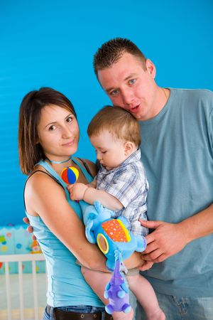 Portrait of happy family at home. Baby boy ( 1 year old ) and young parents father and mother posing together at children's room, smiling. Stock Photo - 5943576