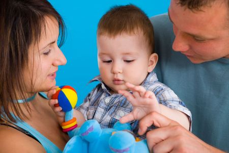 Portrait of happy casual family. Baby boy ( 1 year old ) and young parents father and mother together against blue background, smiling. photo