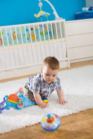 perinola: Beb� (1 a�o de edad) sentado en el suelo en casa y jugar con whirligig.