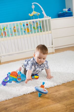molinete: Beb� (1 a�o de edad) sentado en el suelo en casa y jugar con whirligig.