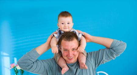 Young father lifting happy baby boy ( 1 year old ) at home, smiling. photo