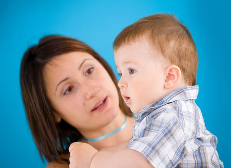 cuddly baby: Young mother carrying baby boy ( 1 year old ) in front of blue background. Stock Photo