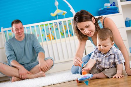 mums: Portrait of happy family at home. Baby boy ( 1 year old ) and young parents father and mother sitting on floor and playing together at childrens room, smiling. Stock Photo