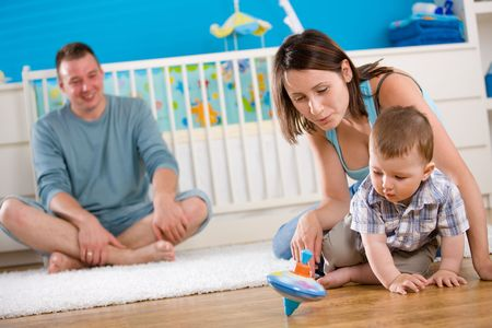 Portrait of happy family at home. Baby boy ( 1 year old ) and young parents father and mother sitting on floor and playing together at children's room, smiling. Stock Photo - 5943600