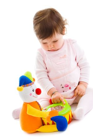 soft toy: Happy baby girl sitting on floor playing with toy smiling, cotout on white background.