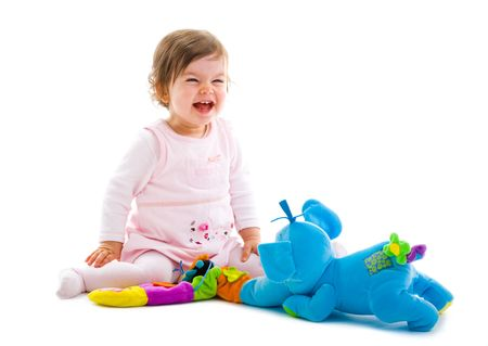 Happy baby girl sitting on floor playing with toy smiling, cotout on white background. photo