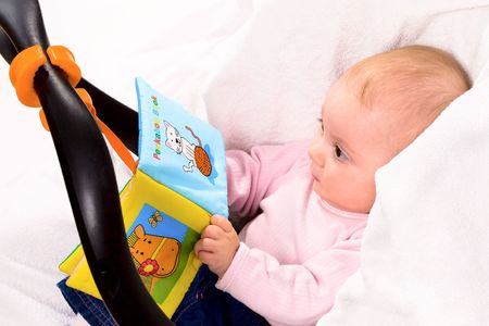 Baby playing with story book sitting in baby carrier. photo