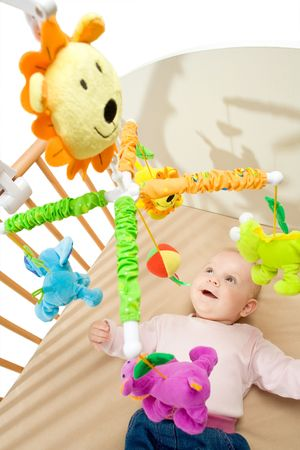 Happy baby playing with bed side toy, smiling. Stock Photo - 5943561