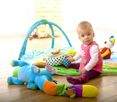 sitting on floor: Baby Girl (9 months old) sitting on floor and playing with toys at home in living room. Toys are property released. Stock Photo