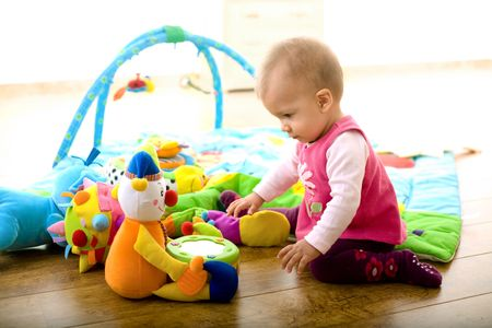 9 months: Baby girl (9 months) playing with soft toys at home. Toys are property released.