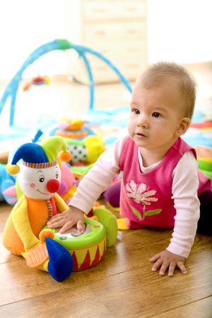 Baby girl (9 months) playing with soft toys at home. Toys are property released.  photo