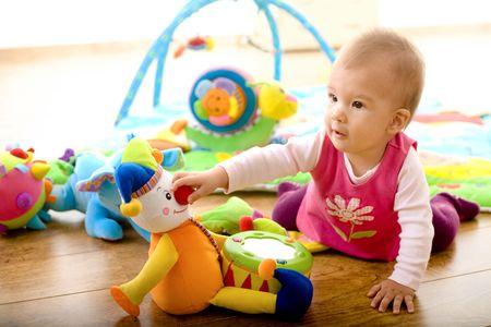 juguetes: Ni�a (9 meses) jugando con juguetes blandos en casa. Los juguetes son propiedad lanzado.  Foto de archivo