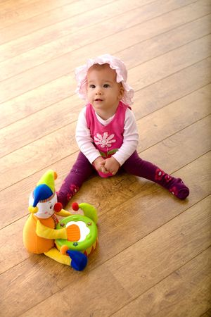 Baby girl (9 months) sitting on hardwood floor together with a toy clown. The toy is property released.  photo
