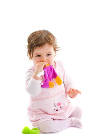 Happy baby girl sitting on floor playing with soft toy, smiling, isolated on white background. Stock Photo - 5943401
